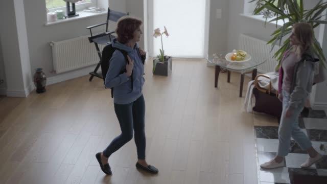 slimmad kvinna med bekväm ryggsäck på ryggen och kvinnan möter henne med stort leende och fixa väskan på bak sidan. - byxor bildbanksvideor och videomaterial från bakom kulisserna