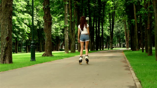 Slim young girl in shorts rollerblading Slim young girl with sexy buttocks in shorts rollerblading charming stock videos & royalty-free footage