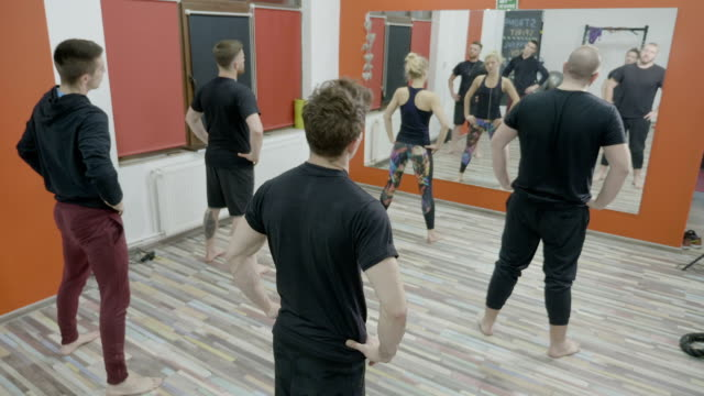 Slim young guys worming up on aerobics class at gym following the exercises of a woman fitness instructor video