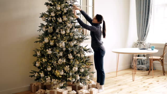 slim young lady is decorating new year tree touching shiny balls and lights standing indoors at home alone. christmas decorations, interior and people concept. - decorare video stock e b–roll