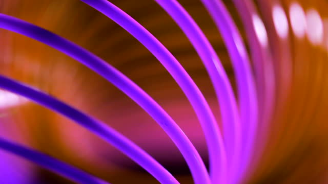 Slinky toy closeup/Plastic toy macro/Colorful spiral lines background
