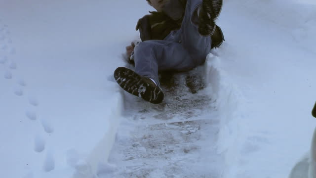 Slip and Fall (HD) Young man walking on an icy sidewalk slips and falls. ice stock videos & royalty-free footage