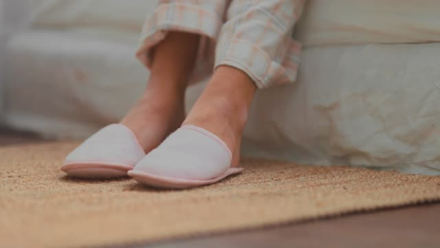 Slippers put on bare feet. Cozy house. Close-up.