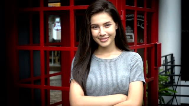 Slo mo - attractive woman smiling to camera. - video
