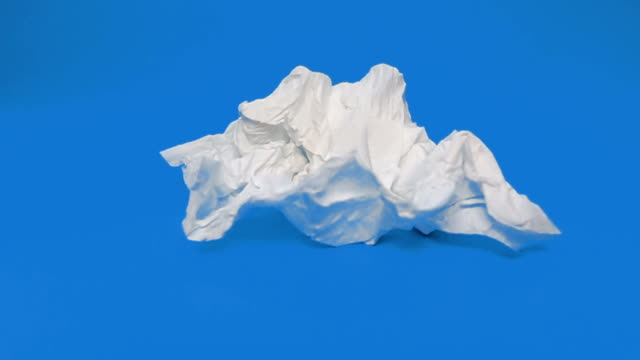 slo mo throwing tissue paper on the floor blue screen background - un singolo oggetto video stock e b–roll