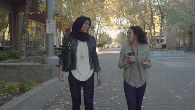 slo mo: two women of middle eastern decent out for a walk in an urban area - scambio d'idee video stock e b–roll
