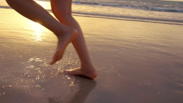 Slomo : Human legs running on the beach video