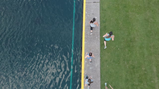 SloMo top-down view of women jogging SloMo top-down view of women jogging next to a pond organized group stock videos & royalty-free footage