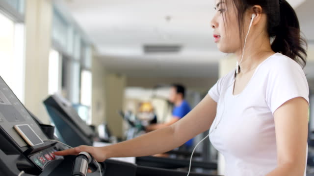stockvideo's en b-roll-footage met slo-mo: sport vrouwen draait op loopband cardio-apparatuur - fitnessapparaat