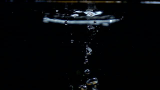 Slo-motion whole orange falling into water video