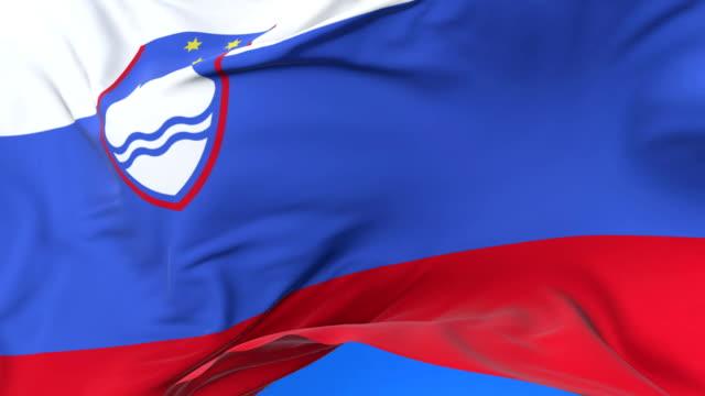 slovenia flag waving at wind in slow in blue sky, loop - styria filmów i materiałów b-roll