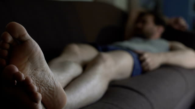vídeos de stock e filmes b-roll de slovenly man in boxers and tank top sleeping on couch, idle life, depression - ignorância