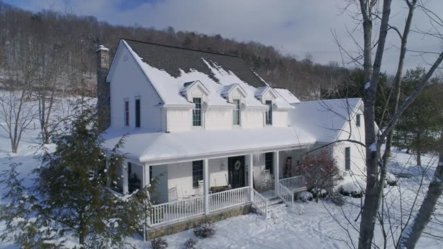 Slow Aerial Reverse of Country House in Winter A slow aerial reverse establishing shot of a typical snow-covered Pennsylvania rural farmhouse in Winter. dormir stock videos & royalty-free footage