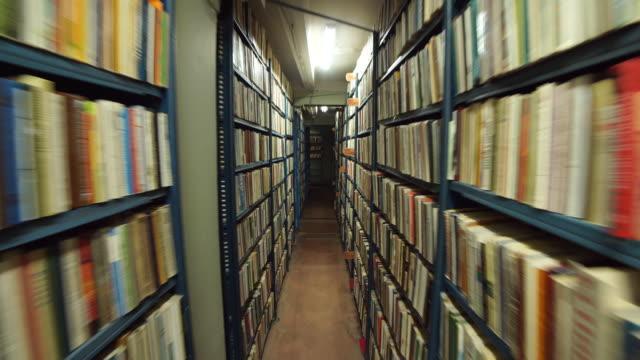 stockvideo's en b-roll-footage met slow camera beweging tussen twee archief planken gevuld met mappen - boekenkast