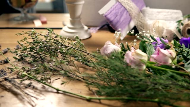 Slow camera movement showing wooden table with flowers, scissors, tapes, decorating paper and other tools for bouquet's arrangement at flower shop. Slowmotion shot video