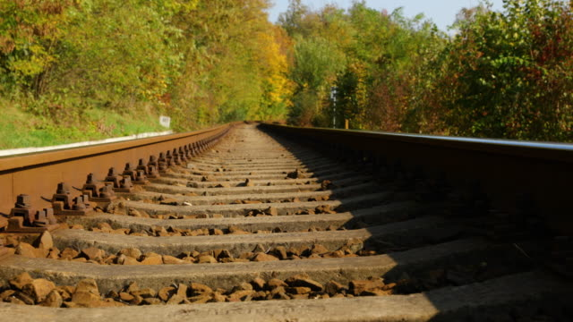 Slow detailed passage between the tracks and a view of the center between the two rails leading forward. Close run from railroad sleepers.
