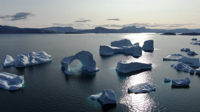 vídeos de stock e filmes b-roll de slow drone aerial view of icebergs floating in the calm baffin sea, greenland - iceberg