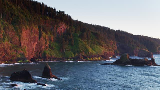 vídeos de stock e filmes b-roll de slow drone flight over rocks and cliffs in cape lookout, oregon - montanha costeira