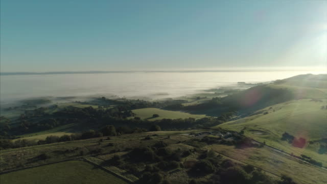 slow drone orbit of ditchling beacon on misty south downs at sunrise - south downs video stock e b–roll