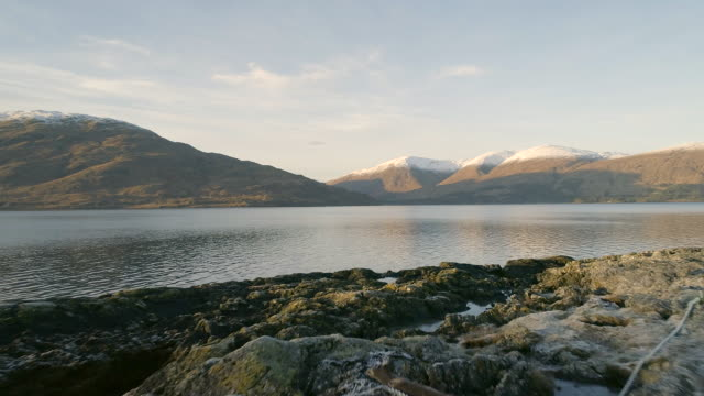 slow flight over the shores of a scottish loch - fort william video stock e b–roll