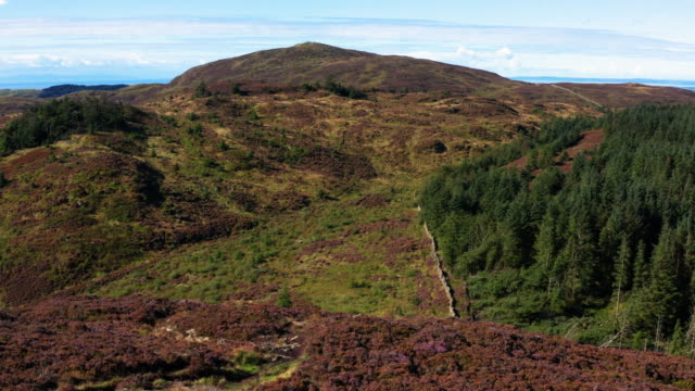 Slow forward dolly shot captured by a drone as it is flown over a cairn on a Scottish hilltop video