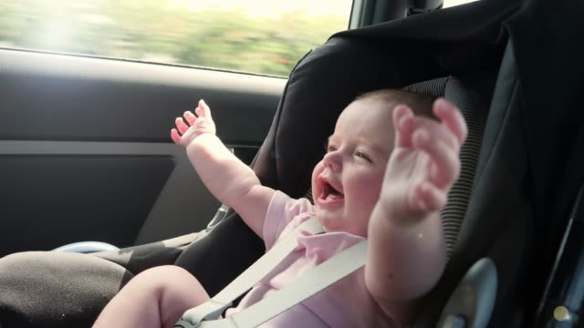 4K Slow: Happy Baby travelling on journey in Car Seat Stock 4K Video clip footage of a baby girl strapped in to a baby car seat in the back of a car. She is happy as the vehicle drives on the journey. Slow motion seat stock videos & royalty-free footage