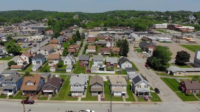 vídeos de stock, filmes e b-roll de devagar abaixando tiro aéreo que institui de pequena cidade bairro residencial - sol nascente horizonte drone cidade