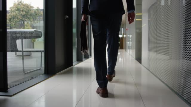 Slow Mo Dolly Businessman Walking Down Office Hallway