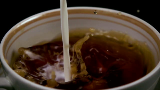 slow mo. in the tea throws sugar and milk flows - english video stock e b–roll