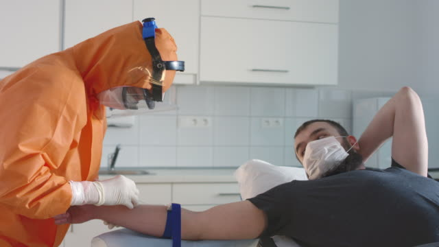 Slow Mo: Nurse in Hazmat Suit Taking Blood Sample from Suspected COVID-19 Patient Zero - Part 1