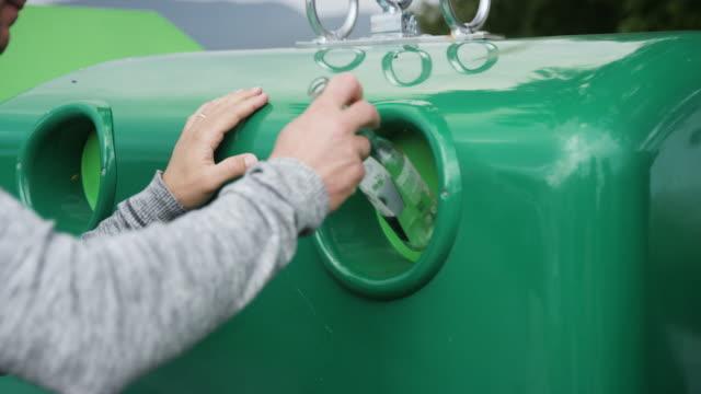 vídeos de stock e filmes b-roll de slow mo of man recycling glass bottles - economia circular