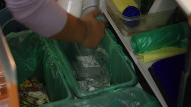 vídeos de stock e filmes b-roll de slow mo of putting plastic into trash - economia circular