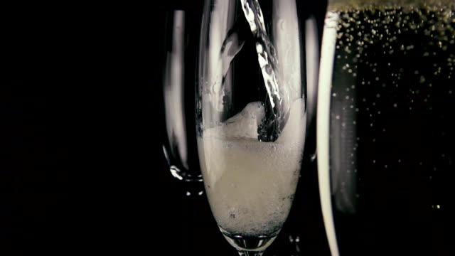 slow mo. one of the three glasses pours champagne wine - bicchiere vuoto video stock e b–roll