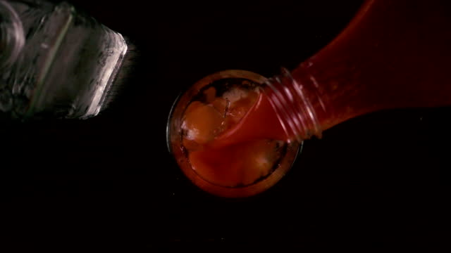 Slow mo. Pour the juice into a glass with ice and vodka top view video