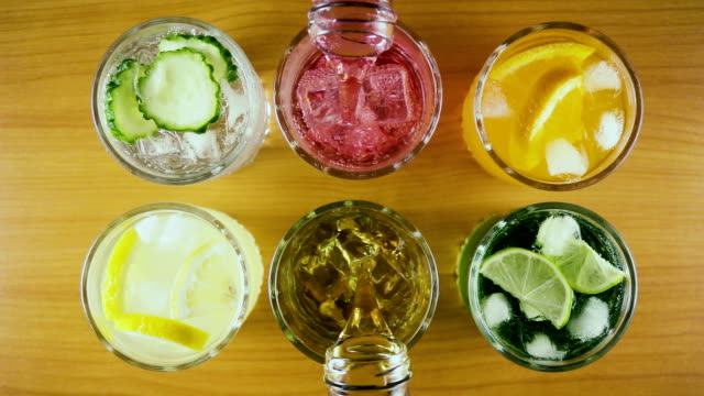 slow mo. six different drinks in two glasses to pour a drink top view - напиток стоковые видео и кадры b-roll