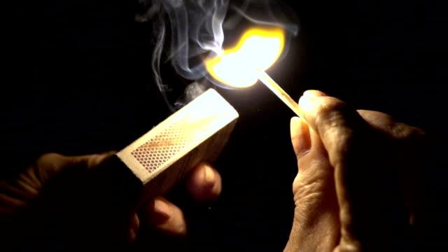 Slow mot: Closeup of hands lighting a match video