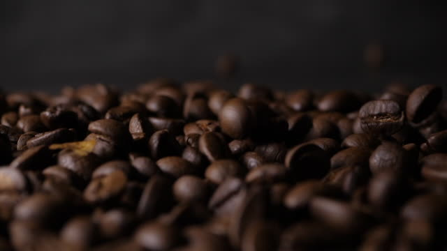 Slow motion 180 FPS Brown roasted coffee beans falling on pile - video