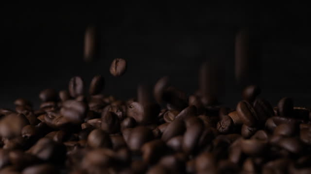 Slow motion 180 FPS Brown roasted coffee beans falling on pile video