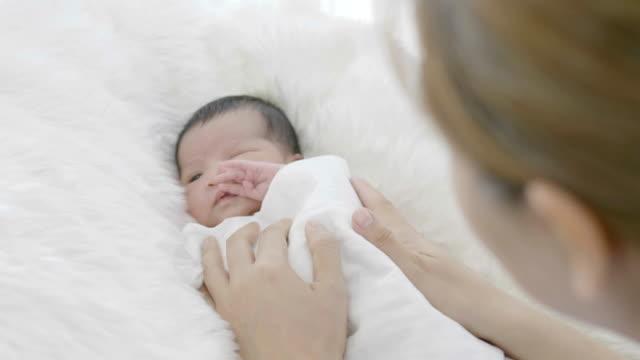 vidéos et rushes de mère de slow motion 4k prendre soin de son adorable bébé nouveau-né soigneusement - 0 11 mois