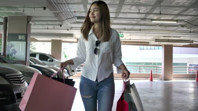 stockvideo's en b-roll-footage met slow motion 4k de mooie vrouw die boodschappentassen in verschillende kleuren vervoert en ze glimlachte gelukkig. dat heeft dingen gekocht die ze leuk vindt, en het is een heldere dag. - aziatische etniciteit
