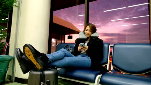 4K Slow motion: A Asian woman Chilling and using smartphone at international airport terminal. Passengers of Transfer Flight waiting for boarding