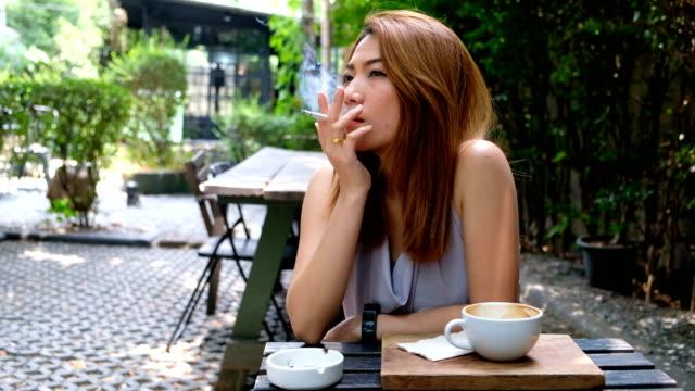 stockvideo's en b-roll-footage met 4k slow motion: een aziatische vrouw roken sigaret in coffee cafe alleen voor ontspanning. - ongezond leven