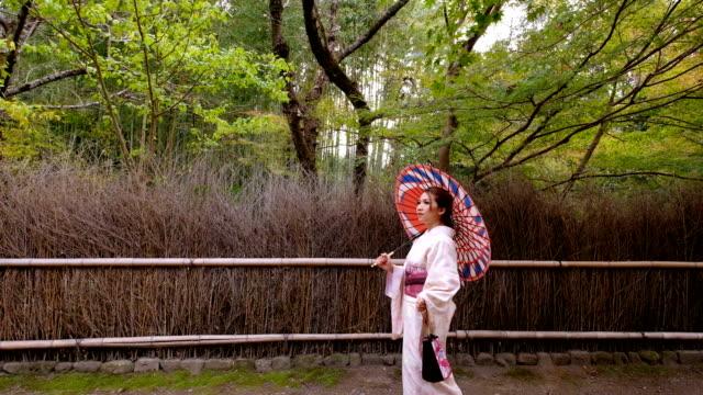 4K Slow Motion : A Asian woman wearing Kimono Dress walking through Bamboo Groves Arashiyama and Sagano. Japanese Culture
