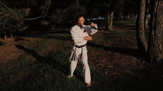 slow motion, a fighter of martial arts, man in kimono with nunchaku,