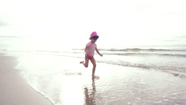 vídeos de stock e filmes b-roll de slow motion: a girl having fun on beach. - descalço