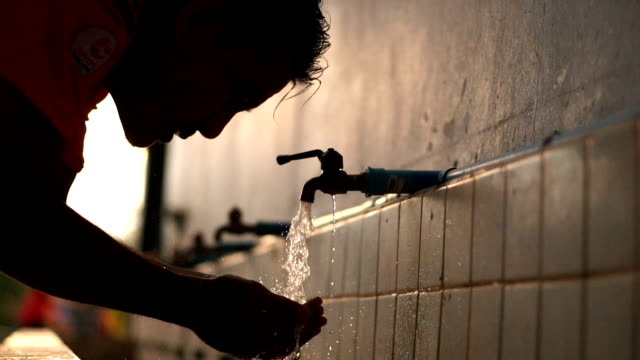 Slow Motion A man who turns on the tap, rinses hands, cleanses face after exercise.