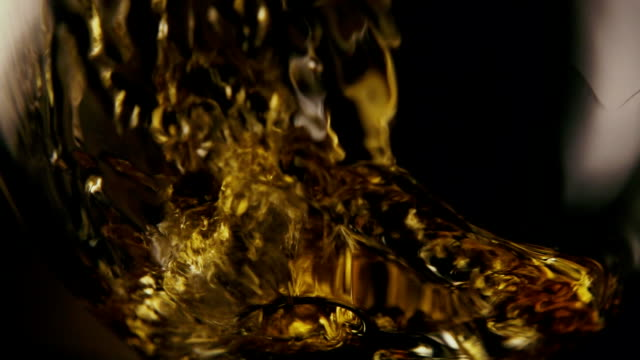 Slow motion. A stream of cognac pours into the glass
