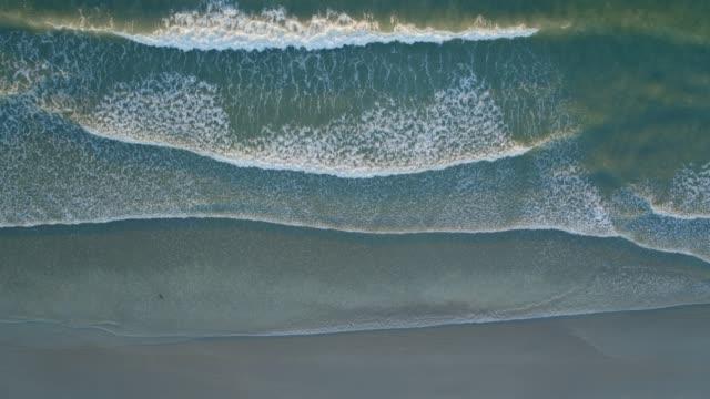 vídeos y material grabado en eventos de stock de abejón aéreo movimiento lento de las olas del mar rompiendo en la costa - marea