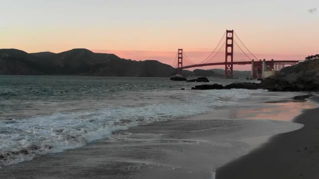 Slow Motion Aerial Video - Baker's Beach in San Francisco, California View of Golden Gate Bridge at Sunset