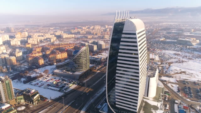 slow motion aerial view drone rotating around corporate office building tower - europa wschodnia filmów i materiałów b-roll